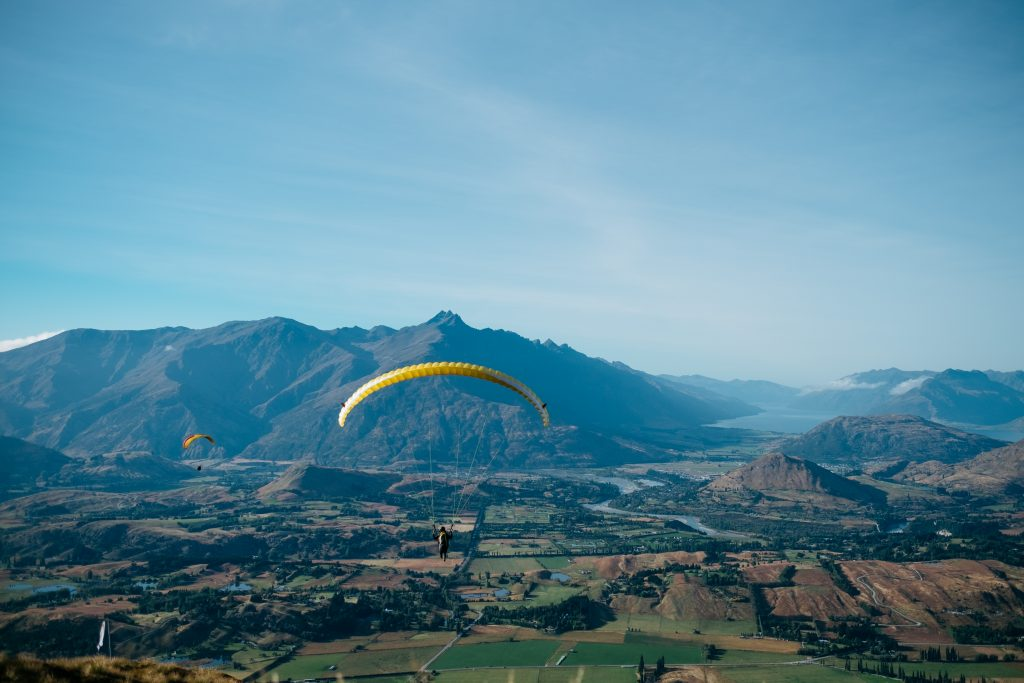 Offer great customer experiences by giving them a chance to share their experience online. Like this person gliding from a parachute over New Zealand