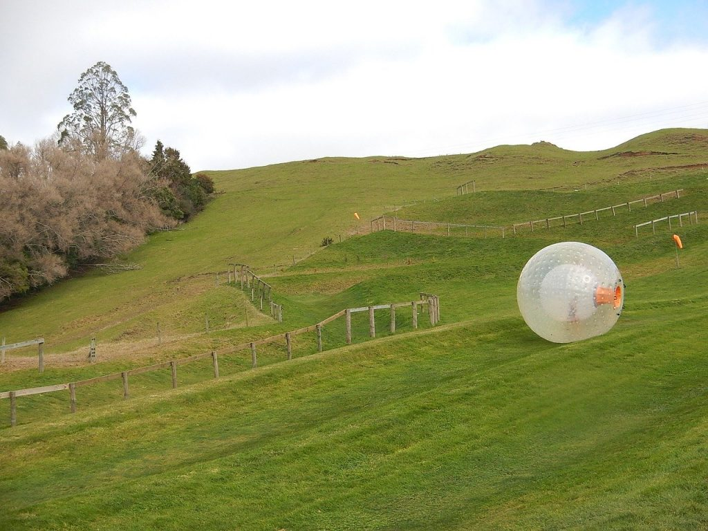 ZORB going down a beautiful green hill in New Zealand